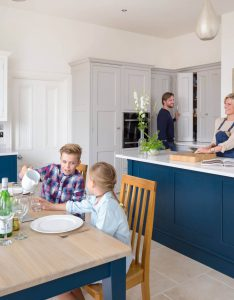 A family of four enjoying breakfast in their luxury kitchen. The mother is cooking at the kitchen island with husband's support whilst the children are eating at a large oak table, laughing between themselves.