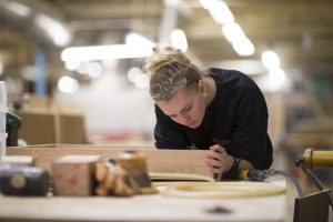 Drew Forsyth Employee focusing on an oak piece of cabinetry to polish every hand crafted detail