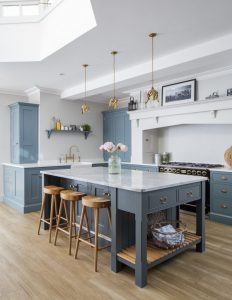 bespoke blue shaker kitchen with a kitchen island, light fixtures and a gorgeous skylight window